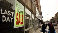 Shoppers walk past row of shops on Kilburn High Road