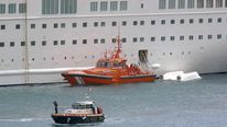 A rescue boat docks by the capsized lifeboat