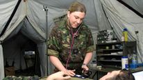 British soldier Tracy Howell, in charge of Tac Medical Wing assists a patient in the camp hospital a..