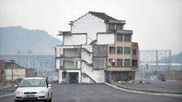 A car drives past a house which stands alone in middle of a newly built road in Wenling, Zhejiang province