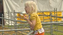 A child eats an ice cream at a country fair