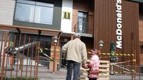 A man and a little girl look at a closed McDonald's in the Crimean capital Simferopol