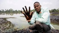 Plaintiff Eric Dooh shows the effects of oil pollution in the village of Goi