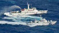 An aerial view shows a Japan Coast Guard patrol ship (C) spraying water at a fishing boat from Taiwan as Taiwan's Coast Guard vessel (top) sprays water near the disputed islands