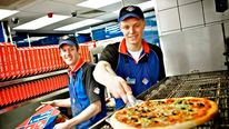 Workers preparing a pizza for delivery