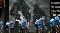 The Garmin cycling team pass a loyalist paramilitary mural painted on a wall in east Belfast as they make their way around the route of the Giro d'Italia team time trial