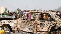 A crowd gathers near a car damaged by a bomb blast just outside Nigeria's capital Abuja