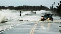 A truck drives through water pushed over a road by Hurricane Sandy in Southampton, New York, October 29, 2012