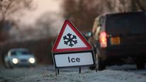 A warning triangle alerts drivers to an icy road