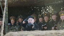 North Korean leader Kim Jong Un (front) watches a drill by the Korean People's Army