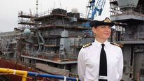 Commander Sarah West in front of HMS Portland