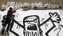 A man works on a graffiti representing the Muslim Brotherhood in Cairo