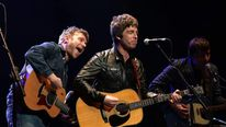 Damon Albarn, Noel Gallagher and Graham Coxon performing on stage together