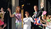 David and Samantha Cameron in Downing Street welcoming the Olympic Torch, being carried by Kate Nesbitt