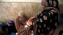 Worker gives polio vaccine