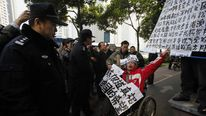 A supporter of the Southern Weekly newspaper in a wheelchair chants slogans in front of police officers near the newspaper's office in Guangzhou