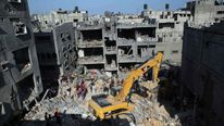 Palestinian emergency personnel dig through the rubble of a building destroyed following an Israeli military strike in Rafah