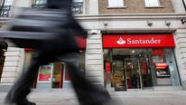A man walks past a Santander branch