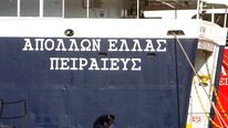 A worker sits beside a ship during a strike in the port of Piraeus
