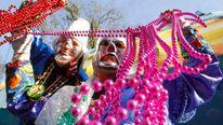Members of the Krewe of Thoth throw beads to Mardi Gras revelers