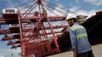 Employee stands next to container ship at Ningbo port in Ningbo