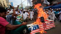 Bangladeshi Muslims shout slogans and kick as they burn a mock coffin of U.S. President Barack Obama during a protest in front of the National Mosque in Dhaka