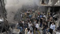 A crowd gathers after a bomb explosion in Damascus