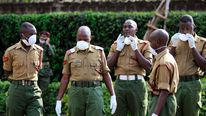 Kenyan police officers wait to receive the bodies of their colleagues