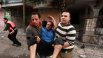 Men carry wounded Palestinian after air strike in Gaza City