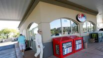 Two customers walk outside the 4 Sons Food Store and Chevron gas station which sold one of two winning Powerball lottery tickets in Fountain Hills, Arizona