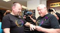 Same-sex couple Bridgesand Michael Snell exchange rings after filling out a marriage license at City Hall in Portland