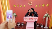 A bridegroom kisses his wife as they pose for pictures under the Chinese national emblem after having their marriage registered at a civil affairs branch office in Wuhan