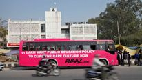 Motorcyclists ride past a bus which is part of an awareness campaign in New Delhi