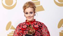 Adele poses with her Grammy award backstage at the 55th annual Grammy Awards in Los Angeles