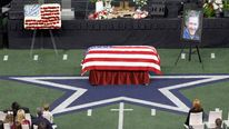 Taya Kyle and children sit near coffin of slain husband former Navy SEAL Kyle during memorial service for former sniper at Cowboys Stadium in Arlington