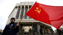 A man holds a Soviet Union flag as he attends a pro-Russian rally at the Crimean parliament building in Simferopol