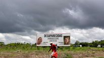 A man walks past a billboard showing the pictures of missing Dutch tourists Lisanne Froon and Kris Kremers on the highway in Boquete