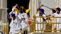 Sikhs wield swords during their clash inside the complex of the holy Sikh shrine, the Golden Temple, in Amritsar