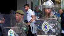 England's Gerrard walks past Brazilian army personnel