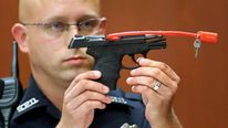 A Sanford police officer holds up the gun used to kill Trayvon Martin