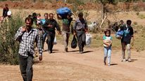 Syrian residents carry their belongings as they cross from Syria into Turkey, near the town of Azaz in Syria