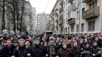 Protesters link arms and shout slogans outside a courthouse in Moscow