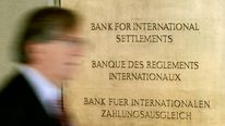 A man walks past a sign in front of the Bank For International Settlements in Basel