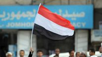 A woman carries the flag of Yemen during a pro-democracy march