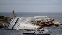 Relatives sail on by the Costa Concordia cruise ship at Giglio island.
