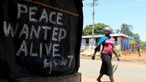 A woman walks past a message of peace in Kibera slum in the capital Nairobi.