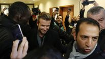 People take photos of soccer player David Beckham at the Pitie-Salpetriere hospital, Paris