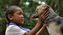 Kabang the snoutless dog with a family member