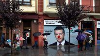 Passers-by walk near a defaced poster of Inigo Urkullu, president of the Basque Nationalist Party
