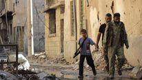 A boy carries a weapon as he walks with members of the Free Syrian Army on a damaged street filled with debris in Deir al-Zor